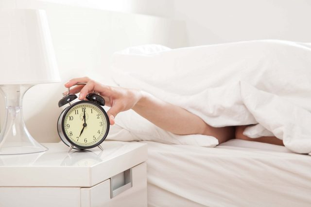 Hand reaching out to alarm clock