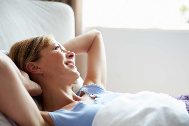 Woman in bed having one of her happier mornings
