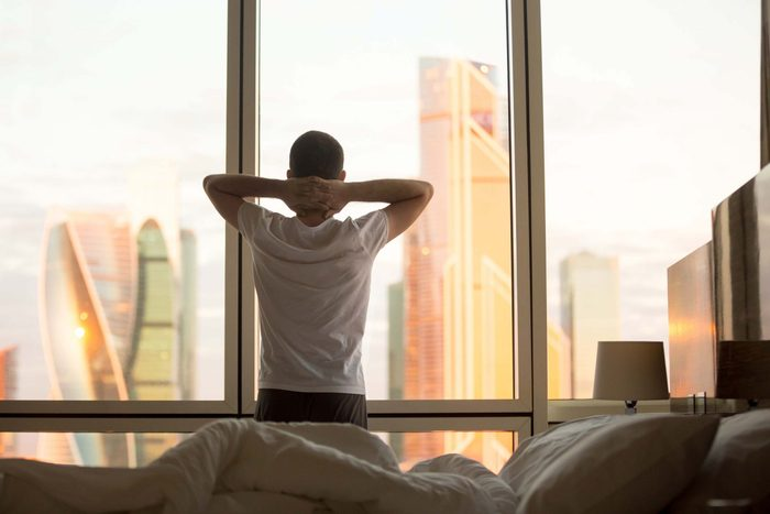 Man stretching next to window in the morning