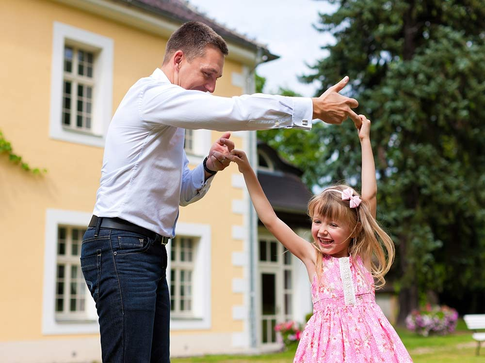 Father and young daughter dancing
