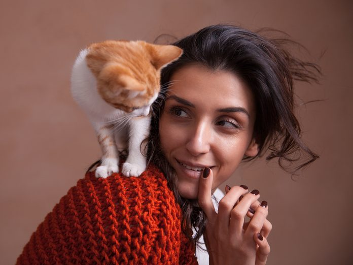 Woman with cat on her shoulder