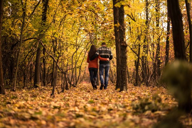 Young couple going for a walk in the park during fall