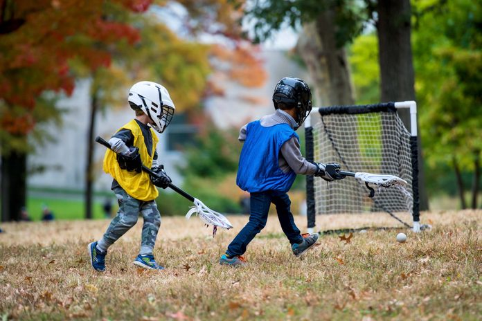 Little kids playing lacrosse in the park during fall