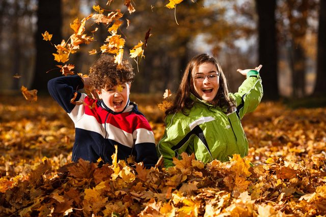 Kids playing in leaves during fall