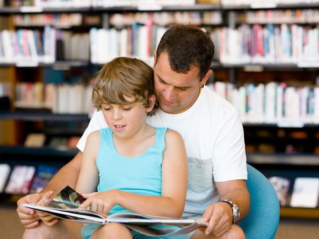 Father and son reading at the library