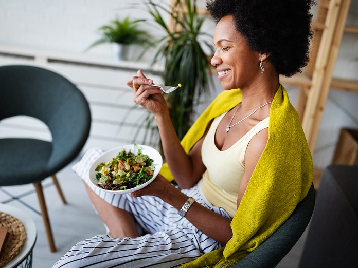 woman eating vegetable salad at home