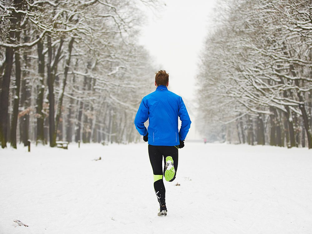 Man running on trail during winter