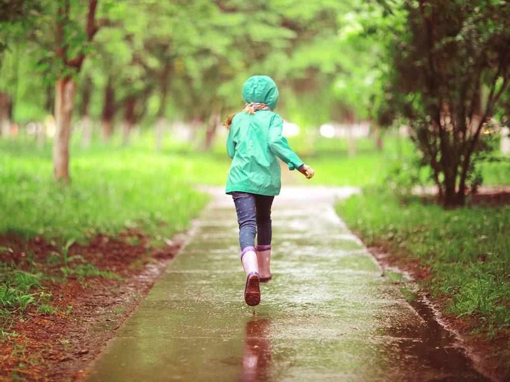Little girl running in spring rain