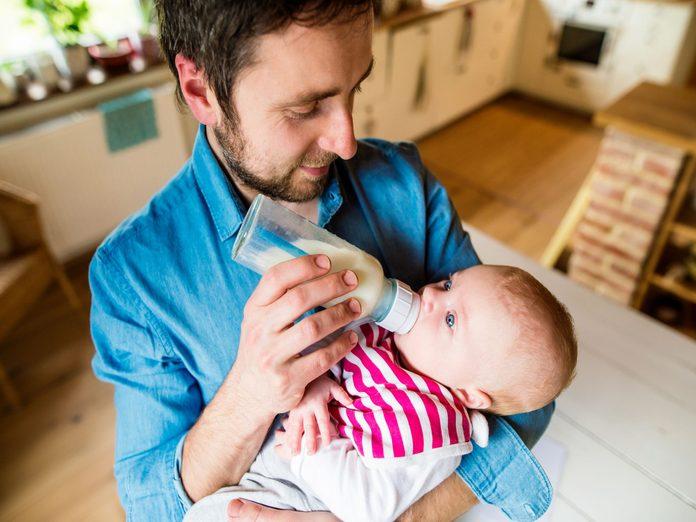 Father feeding his baby milk