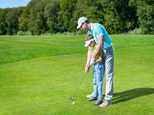 Father helping his son play golf