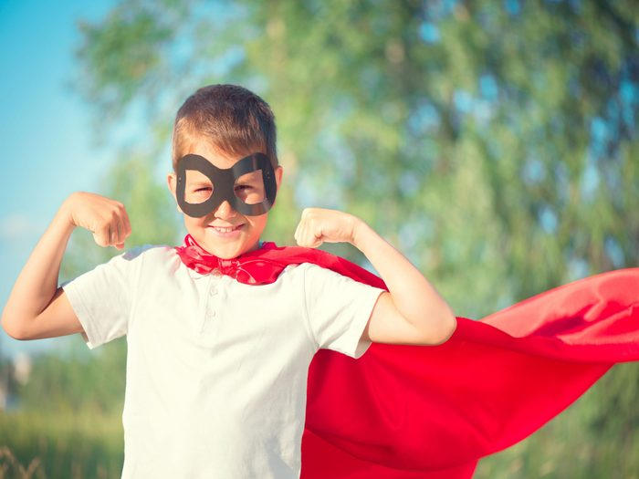Young boy wearing a mask and cape
