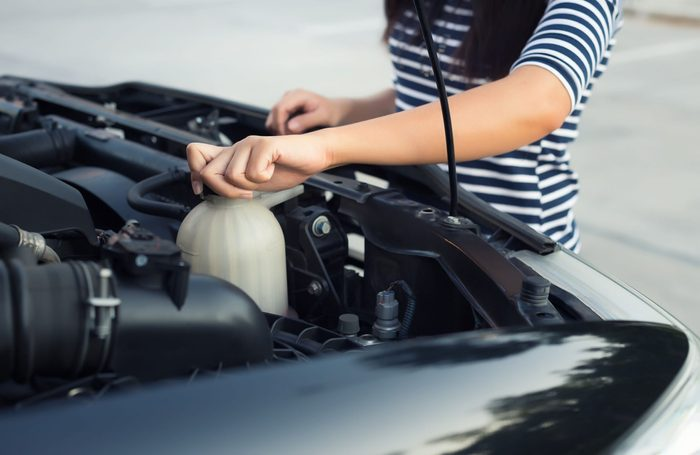 Woman checking engine coolant