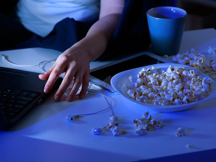 Close-up of spilled popcorn on table and laptop