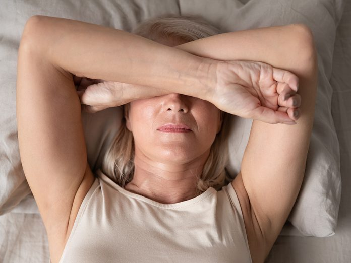 Sleepless mature woman suffering from insomnia close up, lying in bed, older female covering eyes with hands, trying to sleep, nightmares or depression, feeling headache or migraine