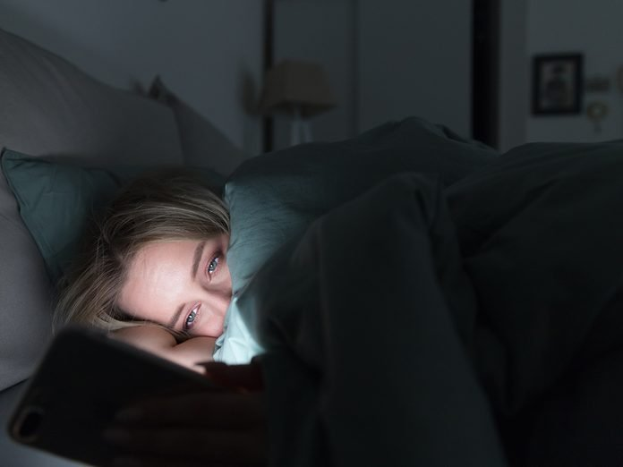 Portrait of young sleepy tired woman lying in bed under the blanket using smartphone at late night, can not sleep/ Insomnia, nomophobia, sleep disorder concept/ Dependency on a cell phone