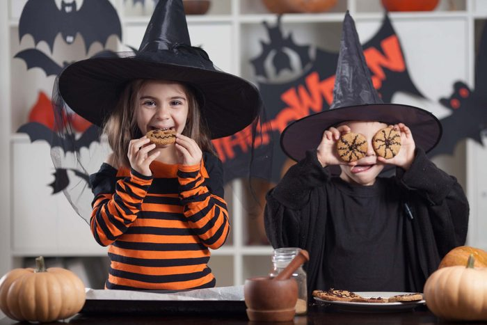 Two children eating cookies at Halloween party