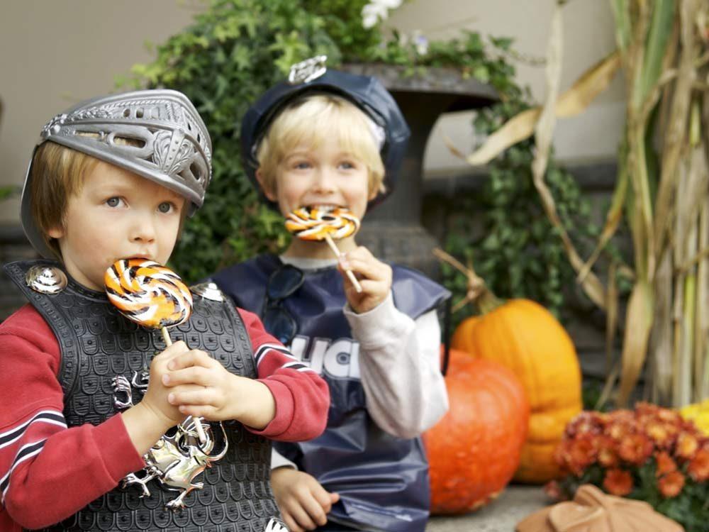 Brothers eating lollipops on Halloween
