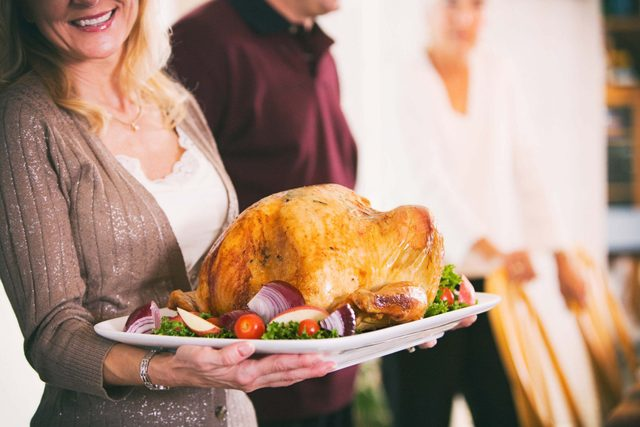 Woman carrying turkey for Thanksgiving dinner