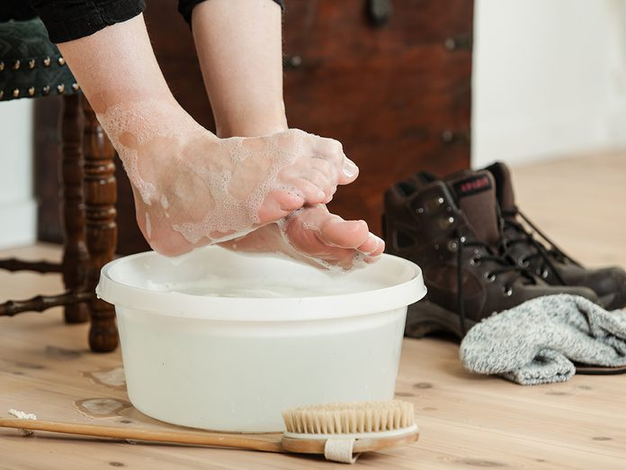 Close up on curled up toes over cold soapy water in plastic bowl and scrubbing brush beside shoes and socks