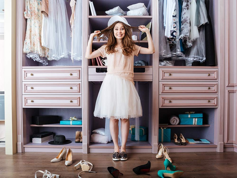 Young girl choosing shoes in her wardrobe