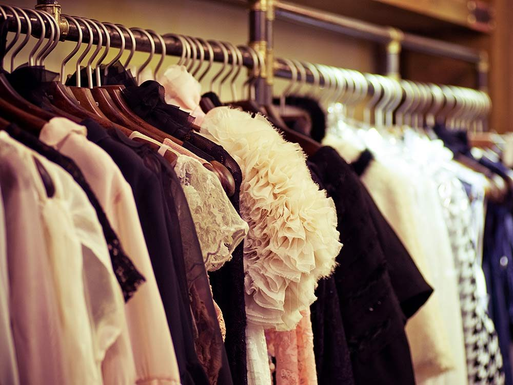 Fashionable clothes on wooden hangers in closet