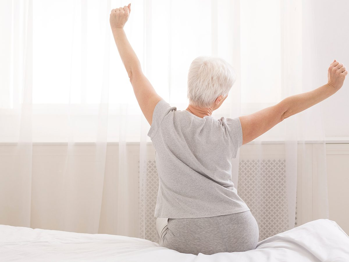 Stiff neck relief - senior woman doing stretches at morning