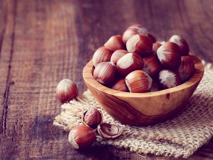 Wooden bowl full of hazelnuts
