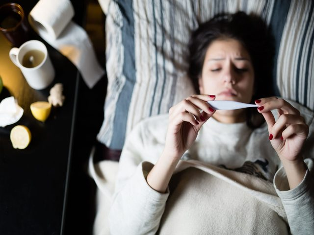 Sick woman lying in bed with thermometer
