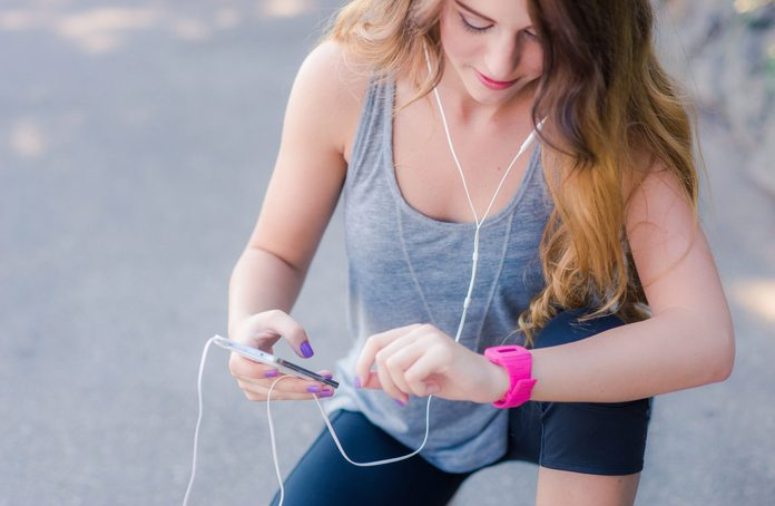 Woman taking a break from exercise and looking at her smartwatch
