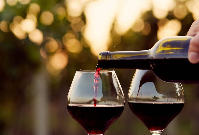 Red wine being poured into two wine glasses