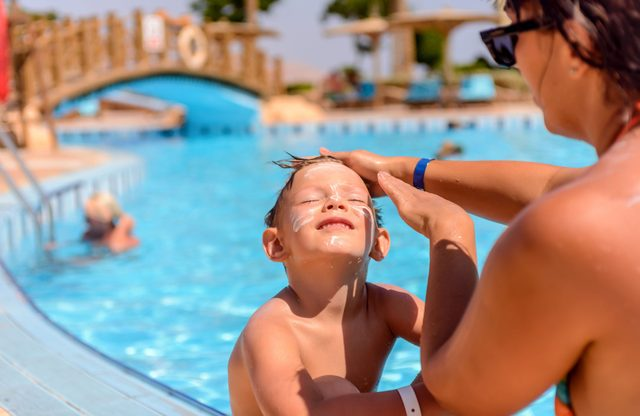 Mother applying sunscreen on her son's face