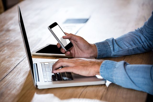 Man using both his smartphone and laptop