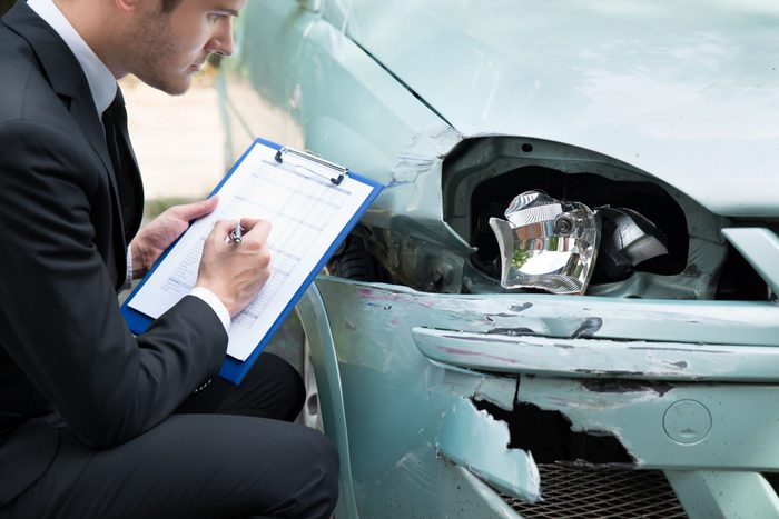 Insurance agent assessing damage on car