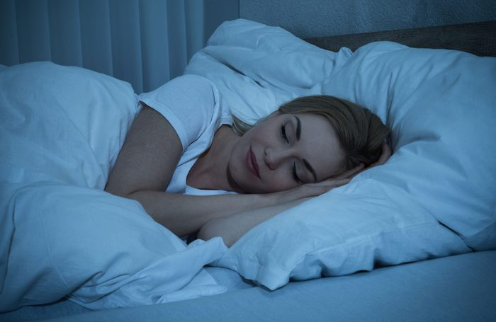Woman sleeping in bed at night