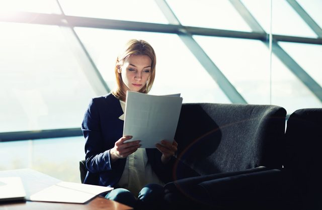 Woman reads files in a boardroom