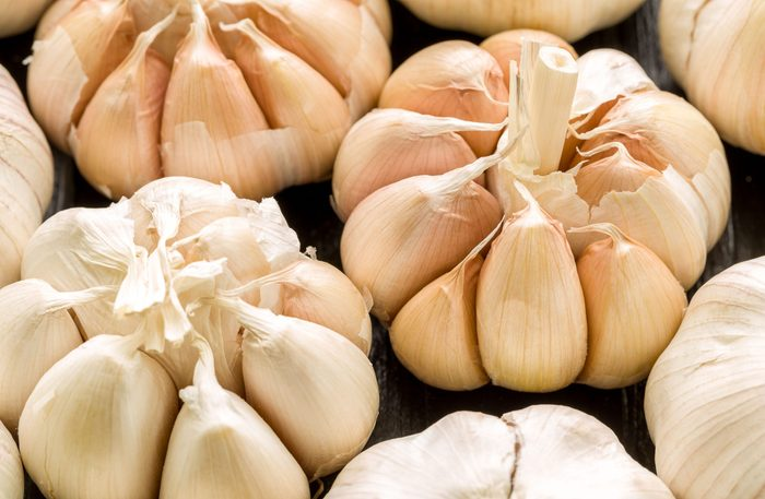 Four heads of garlic against black background