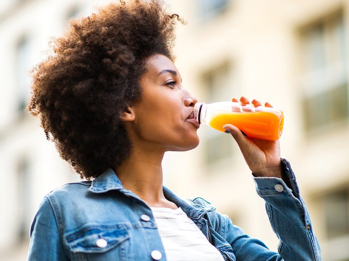 How much water you should drink - woman drinking orange juice