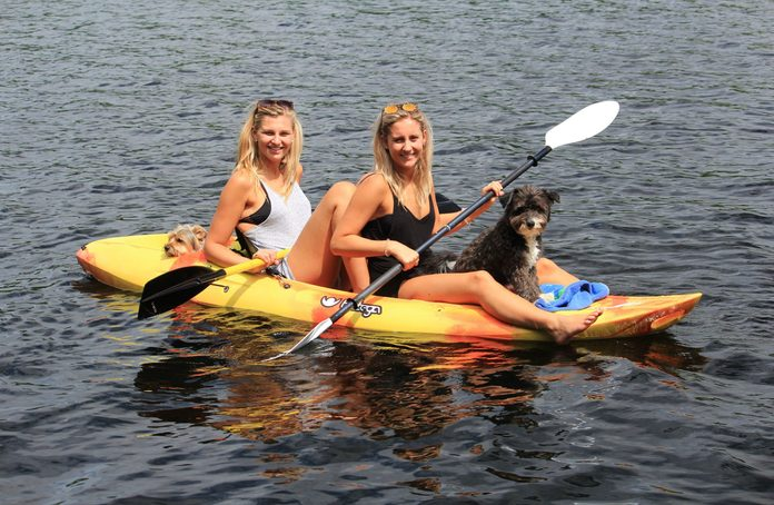 Two women on kayak with two dogs