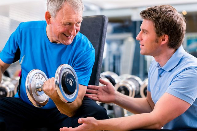Old man exercising with personal trainer