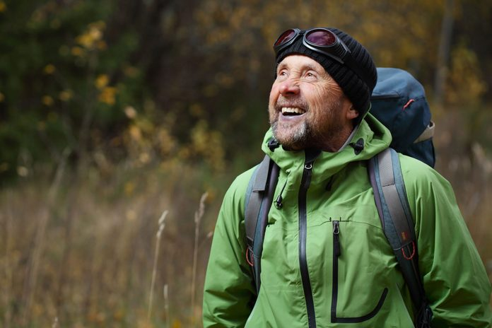 Elderly man hiking happily