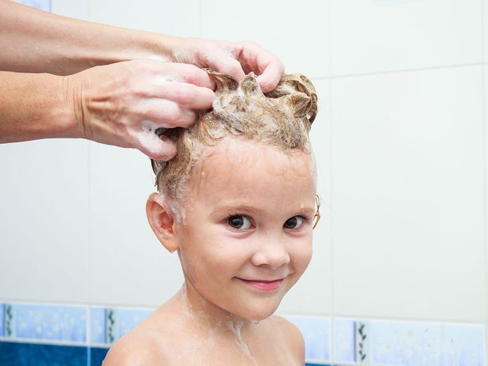 Mother rinsing child's hair with lice treatment