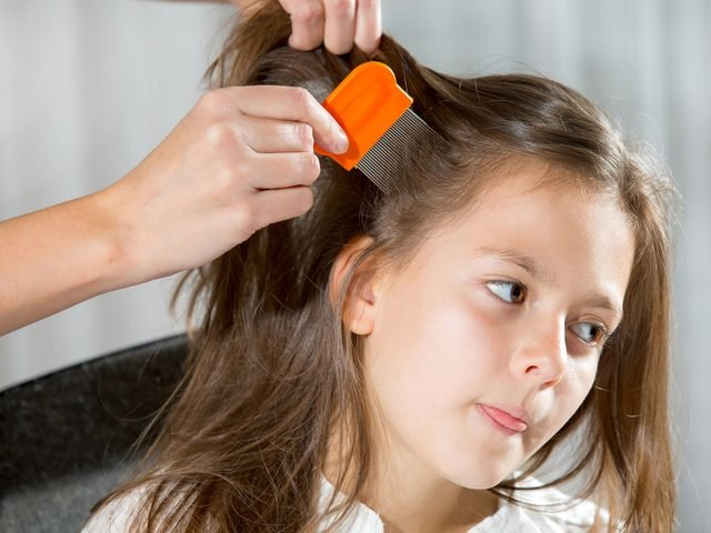 Mother checking child's hair for head lice