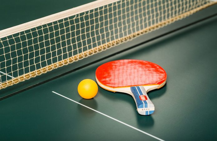 Ping pong paddle and ball on table