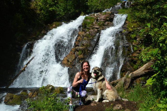 Woman and dog posing near waterfall
