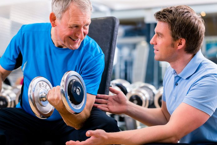 Trainer helping senior work out