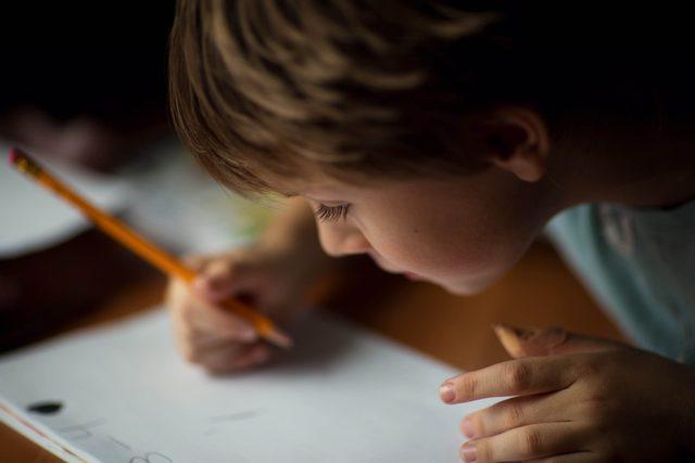Little boy writing letter