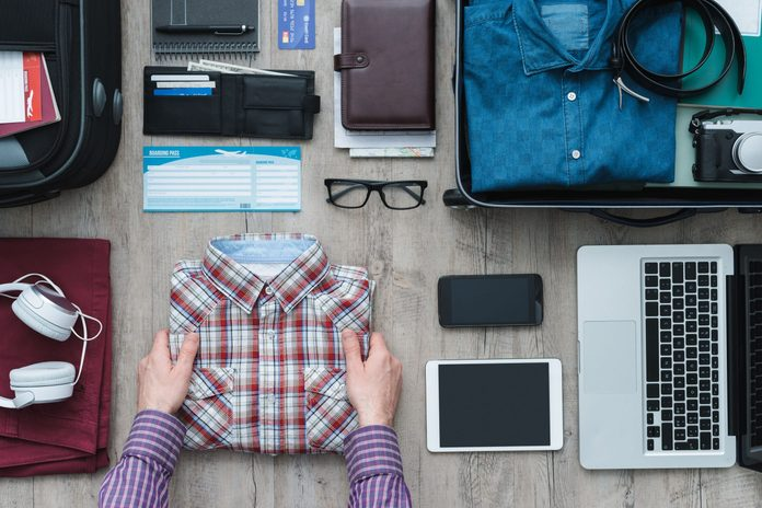 Man packing his clothes for trip