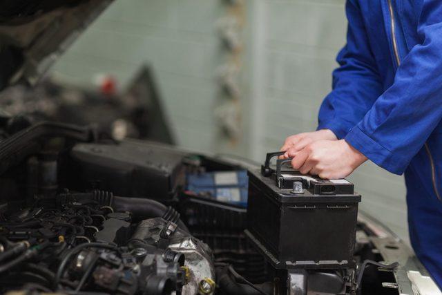 Mechanic checking car battery