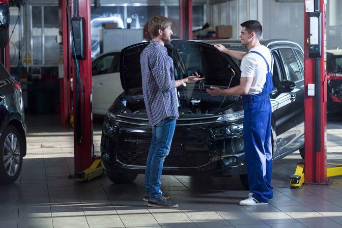 Car owner and mechanic talking at repair shop