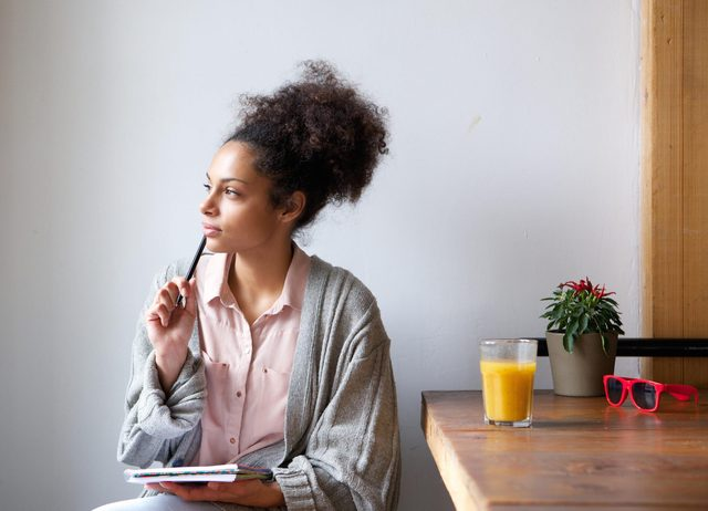Woman thinking with pen and notepad